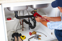 Plumber on the kitchen. Plumber with Plumbing tools on the kitchen. Renovation stock image