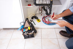 Plumber on the kitchen. Plumber with Plumbing tools on the kitchen. Renovation royalty free stock photography