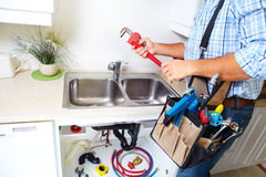 Plumber on the kitchen. Renovation  and plumbing Royalty Free Stock Images