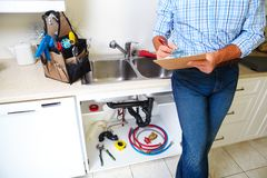 Plumber on the kitchen. Renovation and plumbing royalty free stock photo