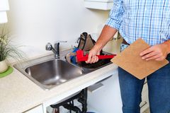 Plumber on the kitchen. Renovation and plumbing royalty free stock photography