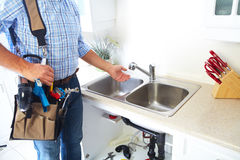Plumber on the kitchen. Renovation and plumbing stock photo