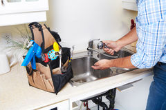 Plumber on the kitchen. Renovation and plumbing royalty free stock image