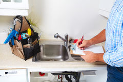 Plumber on the kitchen. Stock Images