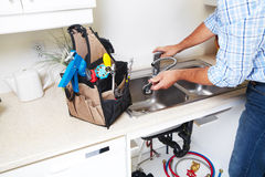 Plumber on the kitchen. Renovation and plumbing stock photography