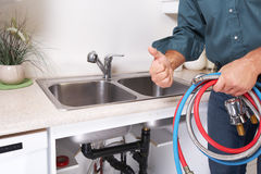 Plumber on the kitchen. Renovation and plumbing stock image