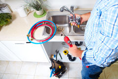 Plumber on the kitchen. Renovation and plumbing stock photos
