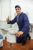 Plumber kneeling next to toilet showing thumb up Stock Images