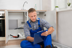 Plumber Looking At Clipboard Stock Image