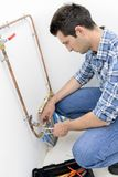 Plumber making adjustments to heating system Royalty Free Stock Photos