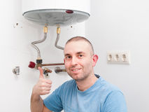 Plumber Man expressing positivity with ok symbol with hand. Man has repaired an electric boiler Stock Photos