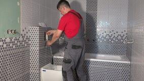 Plumber man flush water from tube of toilet flushing mechanism. Worker install toilet flush button in new modern bathroom. Static shot stock video