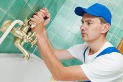 Plumber man repair leaky faucet tap Stock Photography