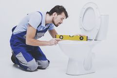 Plumber measures the toilet. Workman with building level during work royalty free stock image