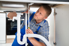 Plumber Measuring Sink Pipe Royalty Free Stock Photography