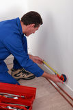 Plumber measuring a wall Royalty Free Stock Photography