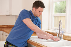 Plumber Mending Tap With Adjustable Wrench. Plumber Fixes Tap With Adjustable Wrench Stock Photo