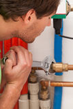 Plumber mending valves. In a boiler room Stock Image
