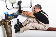 Plumber near water pipes opening water tap stock image
