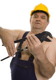 Plumber with pipe wrench and safety helmet Royalty Free Stock Photography