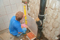 Plumber placing tiles Royalty Free Stock Images