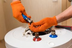 Plumber with pliers fix wires of water heater. Master hands in orange gloves fixing old boiler stock photography