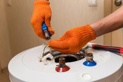 Plumber with pliers fix wires of water heater. Master hands in orange gloves fixing old boiler royalty free stock images