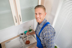 Plumber With Plunger In Kitchen Stock Image
