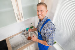 Plumber With Plunger In Kitchen Royalty Free Stock Photos