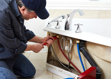 Plumber. Professional plumber doing plumbing renovation in bathroom Royalty Free Stock Image