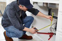 Plumber. Professional plumber doing plumbing renovation in kitchen home stock photography