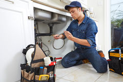 Plumber. Professional plumber doing renovation in kitchen home royalty free stock images