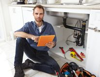 Plumber. Professional plumber doing renovation in kitchen home Stock Photos