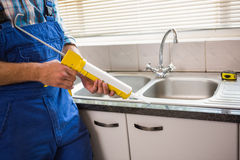 Plumber putting filling in between tiles Royalty Free Stock Photography
