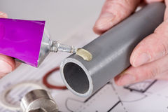 Plumber putting glue on a pvc pipe Royalty Free Stock Photography
