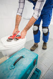 Plumber putting his tools on toilet Stock Photography