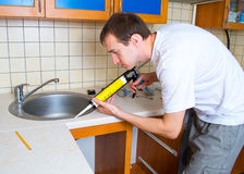 Plumber putting a silicone sealant Royalty Free Stock Images