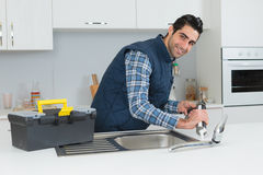 Plumber putting silicone sealant around sink Stock Photo