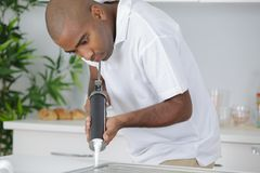 Plumber putting silicone sealant to installing kitchen sink Royalty Free Stock Image