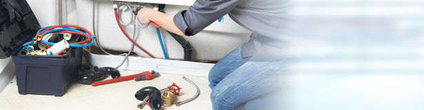 Plumber. Plumber repairing a bath. Construction and renovation background stock photography