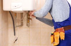 Plumber repairing boiler. In bathroom royalty free stock photo