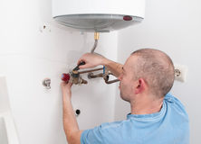 Plumber repairing an electric boiler Royalty Free Stock Image