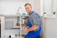 Plumber Repairing Faucet In Kitchen. Happy Male Plumber Repairing Faucet In Kitchen Sink royalty free stock photo