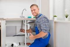 Plumber Repairing Faucet In Kitchen Royalty Free Stock Photo