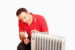 Plumber repairing a heater. Portrait of a man trying to repair a heater royalty free stock photo