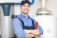 Plumber repairing an hot-water heater royalty free stock photo