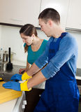 Plumber repairing kitchen sink for  woman Royalty Free Stock Photography