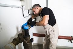 Plumber repairing metallic water pipes and looking inside stock images