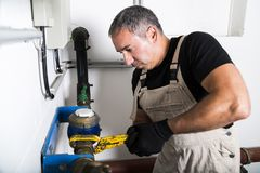 Plumber repairing metallic water pipes with wrench royalty free stock images