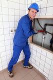 Plumber repairing pipes Royalty Free Stock Photos